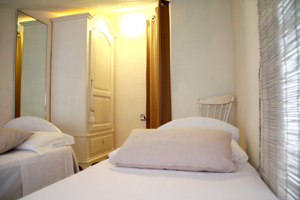 4th mezzanine bedroom with two single beds, with a view of CalaCaterina bay