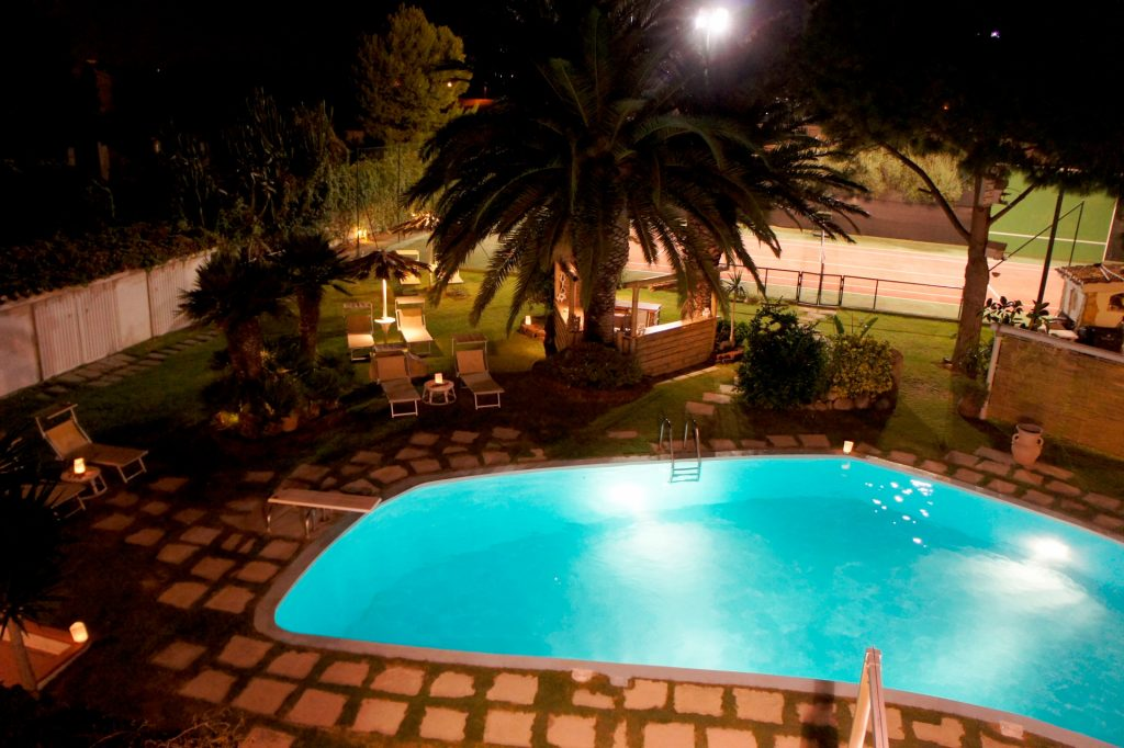 swimming pool and tennis court at night