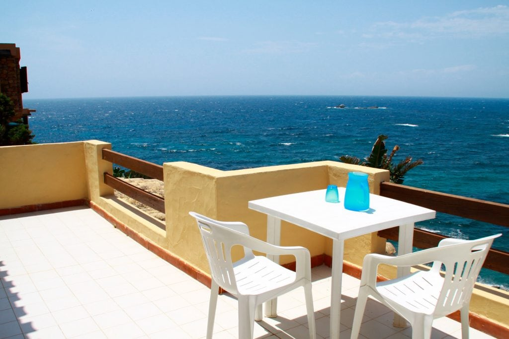 one of the terraces with stunning views of the bay, the beach and sunset front